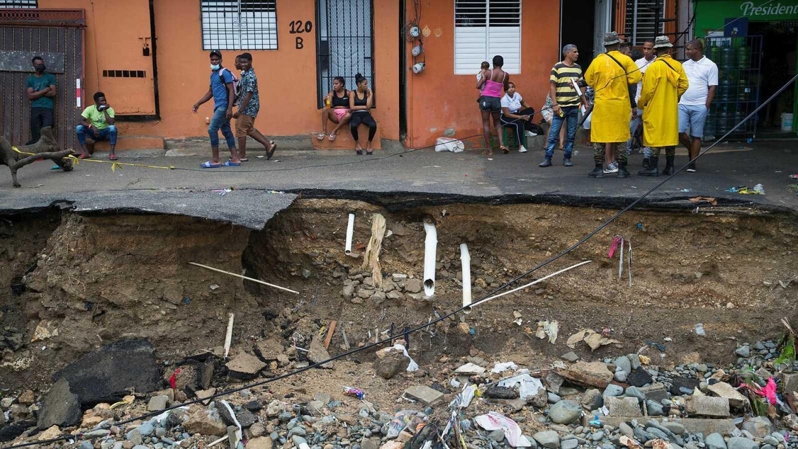 Militares controlan que residentes no se acerquen a la orilla de una calle destrozada debido a las intensas lluvias causadas por la tormenta Laura en Santo Domingo (República Dominicana).