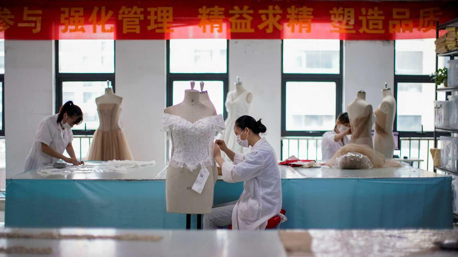 Empleados trabajan en prendas de vestir en una fábrica en Suzhou, provincia de Jiangsu, China.