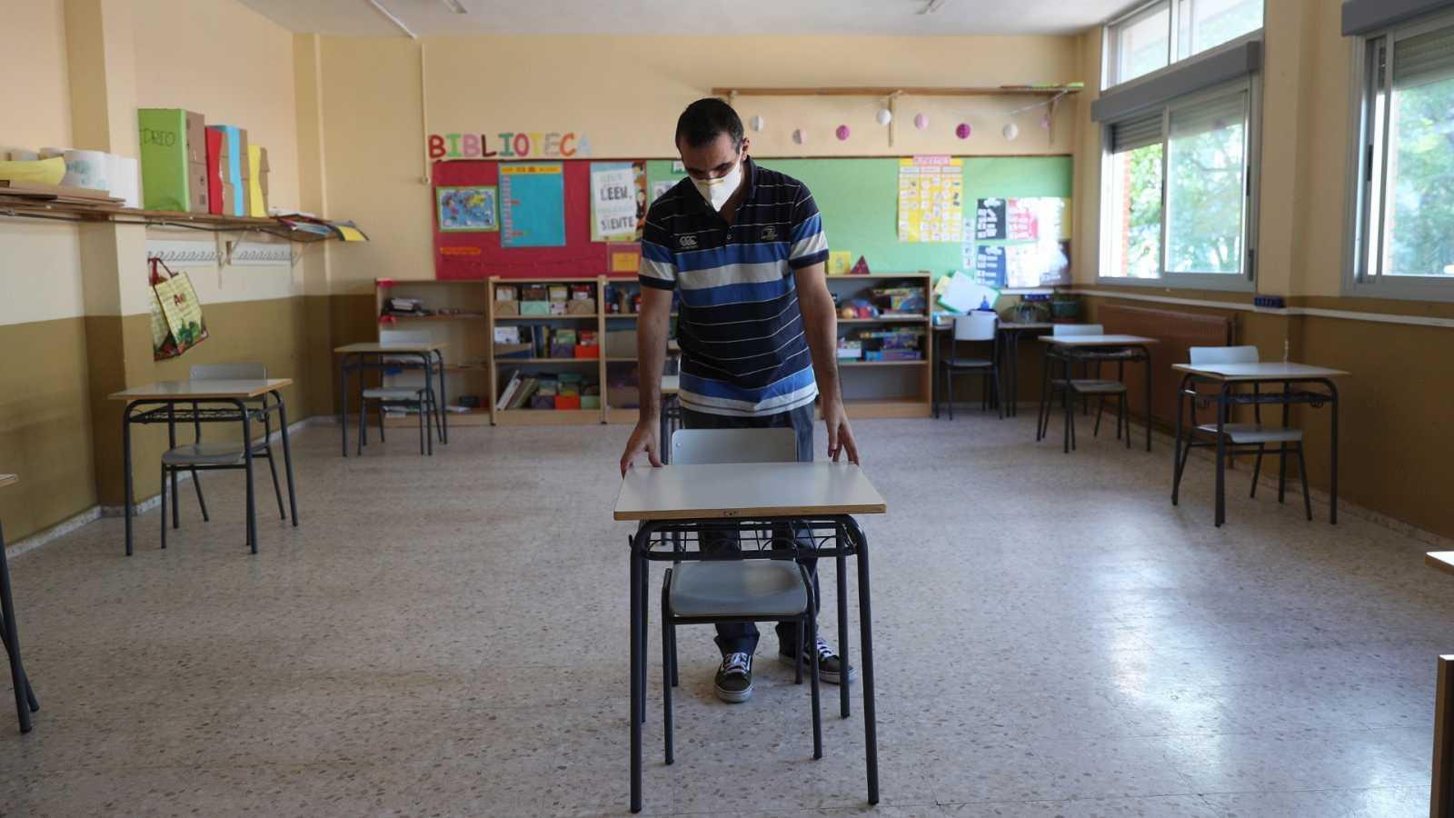 Un profesor coloca las mesas para mantener la distancia de seguridad en un colegio de Torrejón de Ardoz