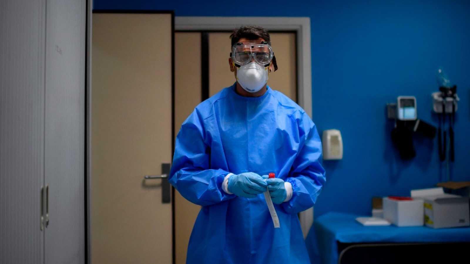 Un sanitario, con equipo de protección, sostiene una muestra en un centro de pruebas en Madrid, este agosto.
