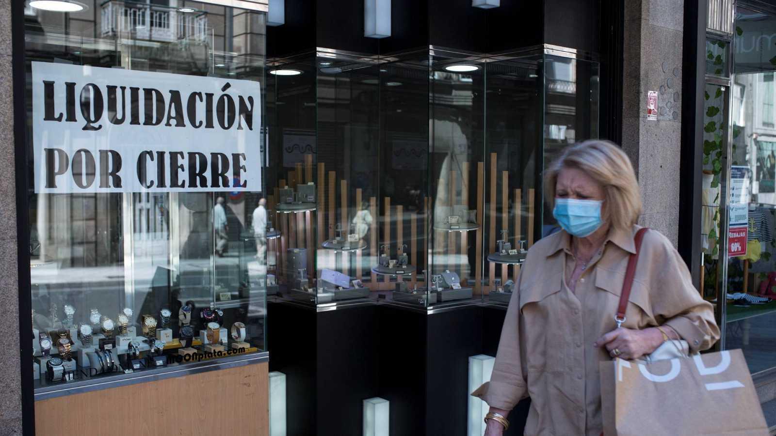 """Una mujer con mascarilla pasa ante un comercio con un cartel de """"liquidación por cierre"""" en Ourense"""