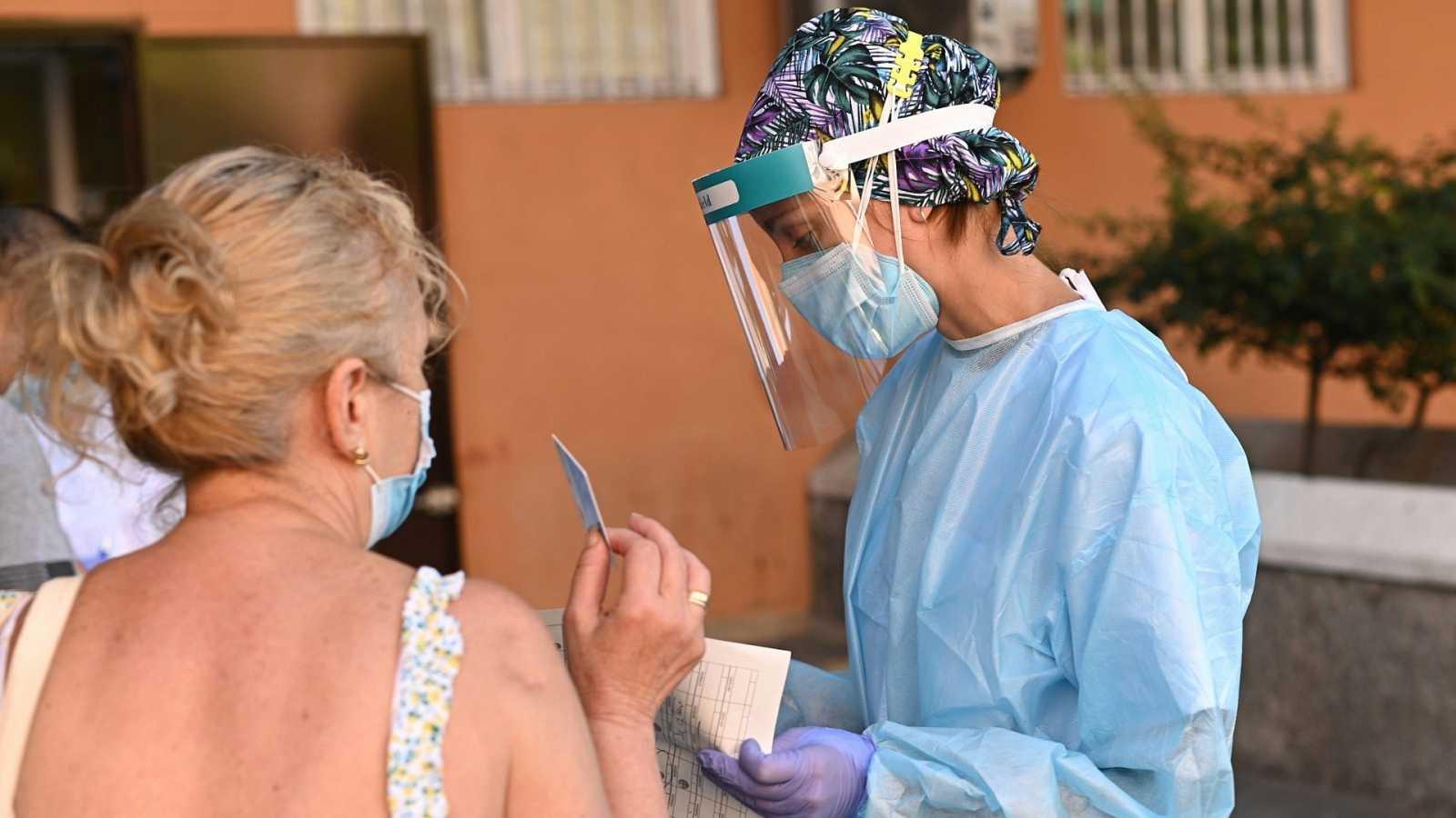 Una sanitaria atiende a una mujer en un centro de salud de Carabanchel