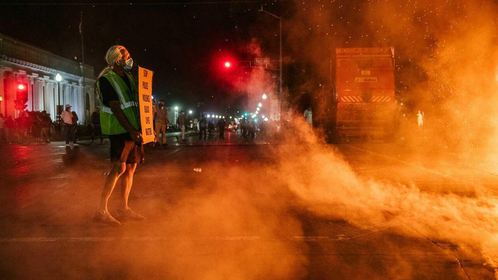 Un hombre está parado con un cartel en Kenosha, Wisconsin en la segunda noche de disturbios después del tiroteo de Jacob Blake.