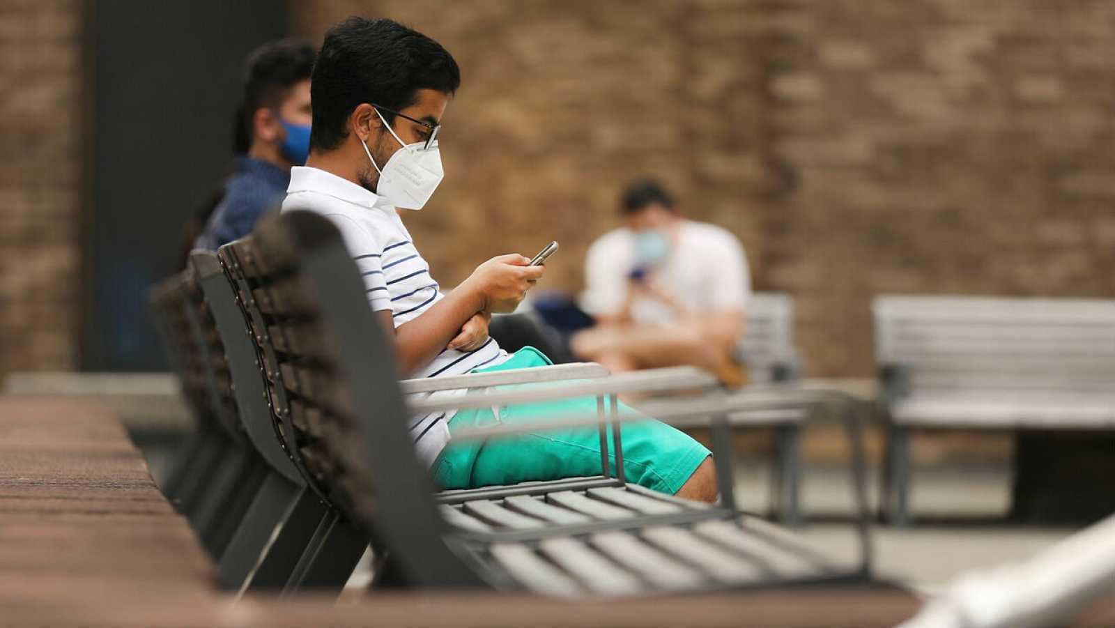 Un estudiante espera fuera de una carpa para hacerse la prueba del COVID-19.