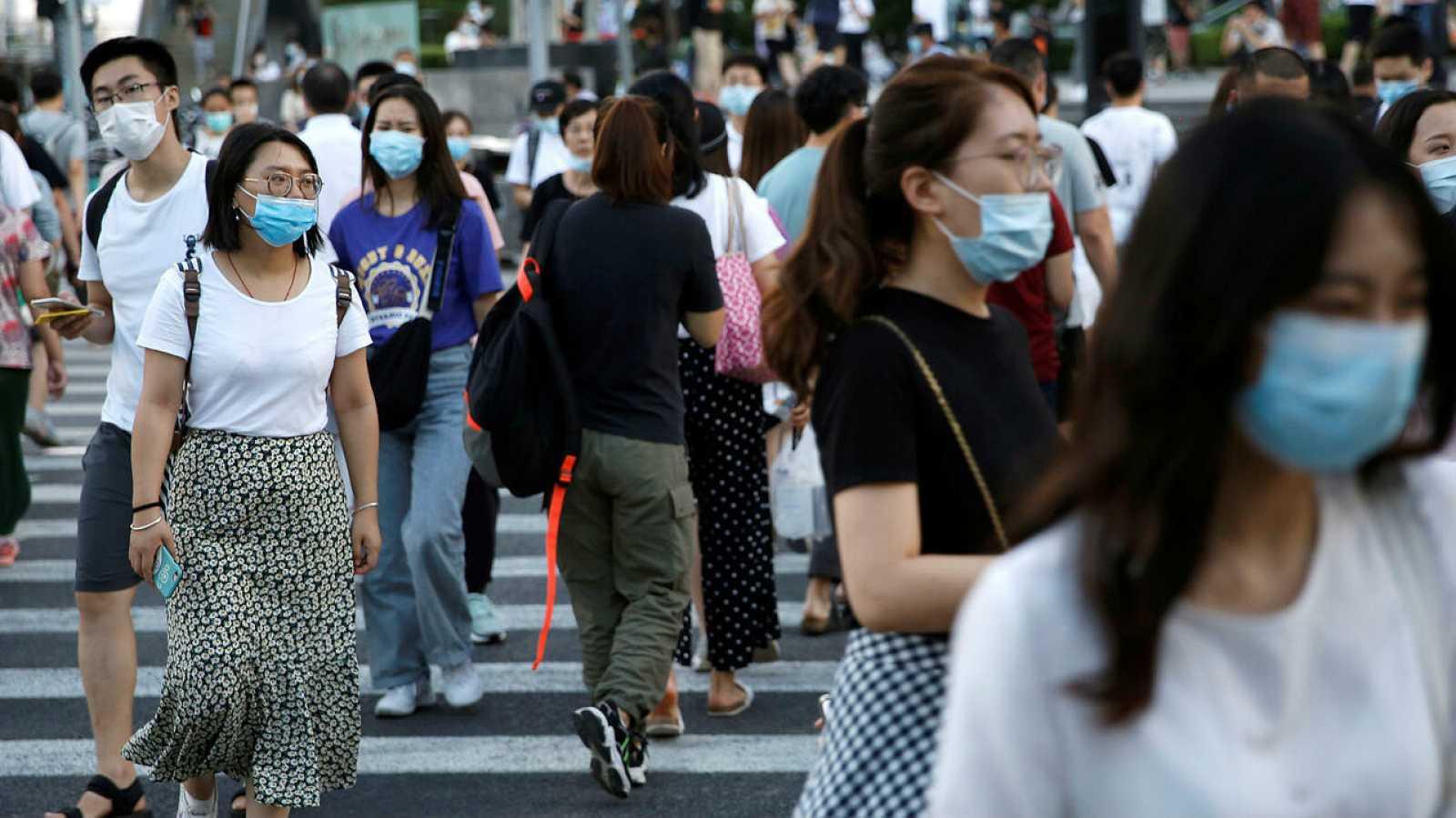 Personas con mascarillas cruzan una calle en un área comercial en Beijing, China.