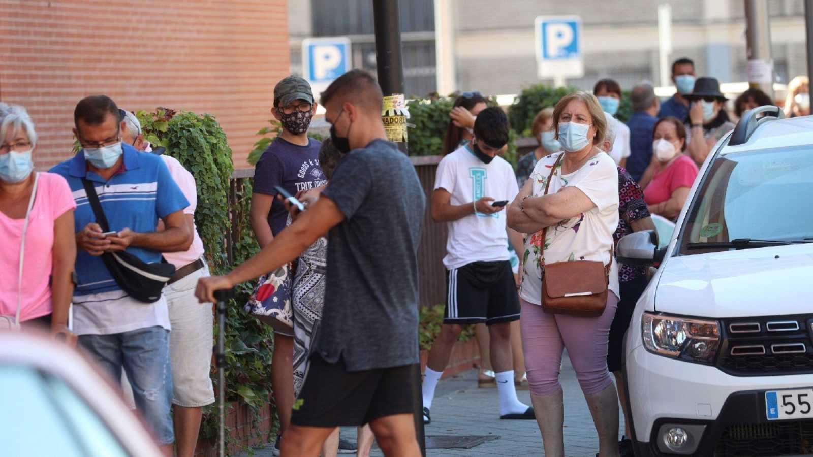 Varios vecinos hacen cola ante un centro sanitario para realizarse una prueba PCR en el distrito madrileño de Villaverde, este miércoles.