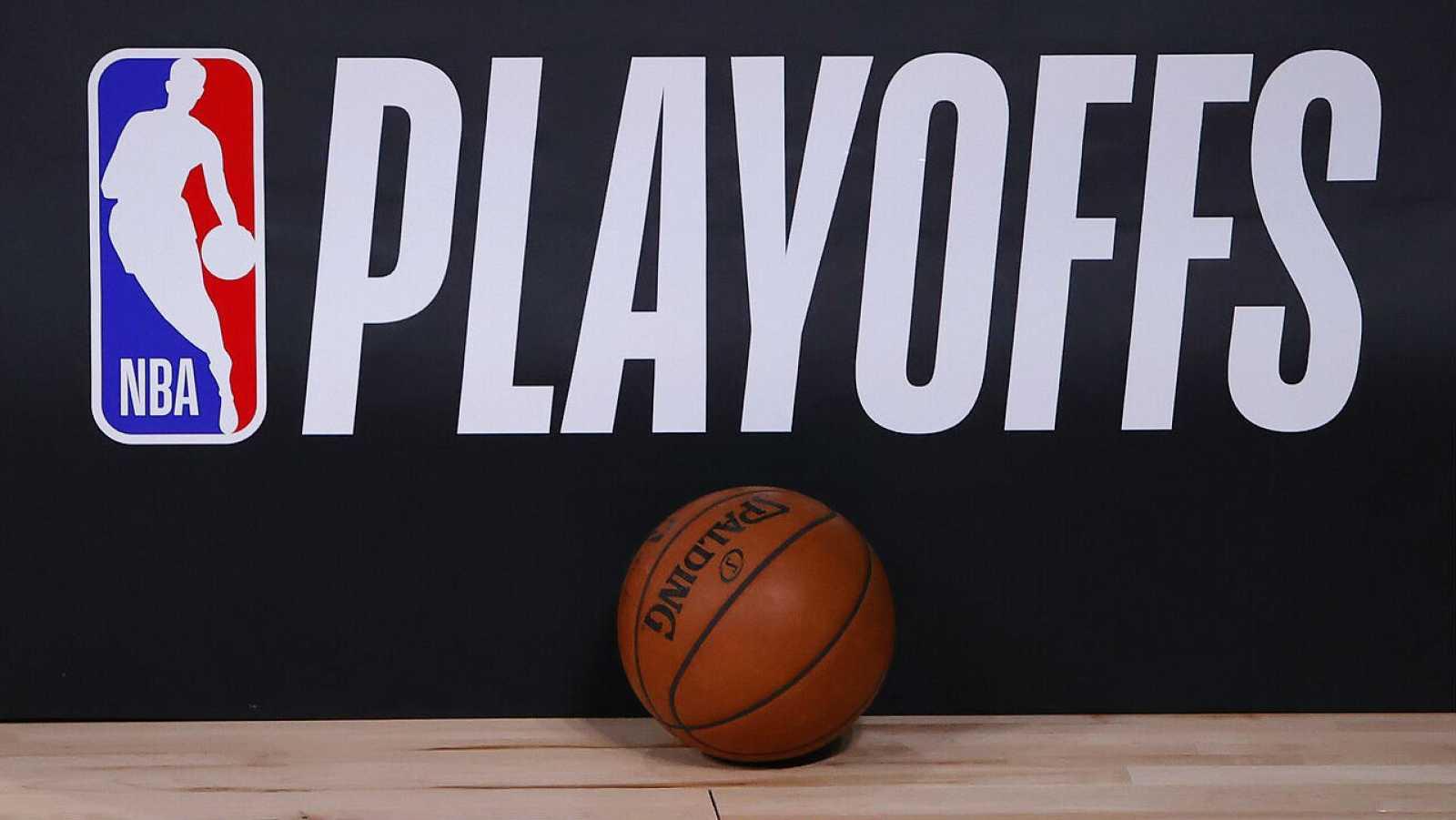 Una pelota de baloncesto se encuentra junto al logotipo de los Playoffs de la NBA.