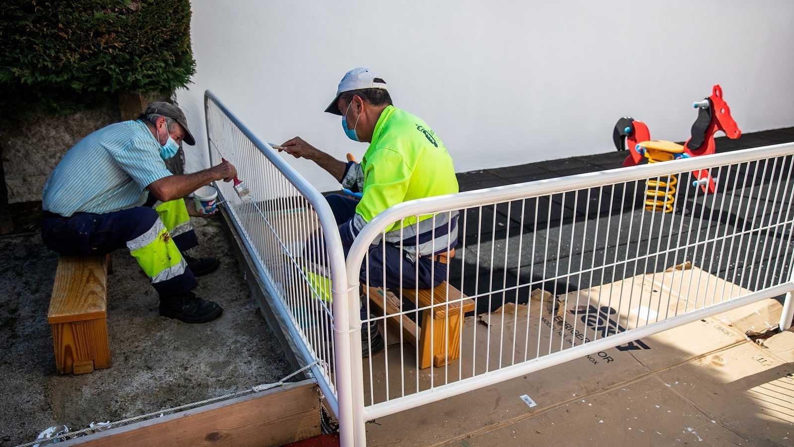 Dos operarios repintan una valla en una escuela