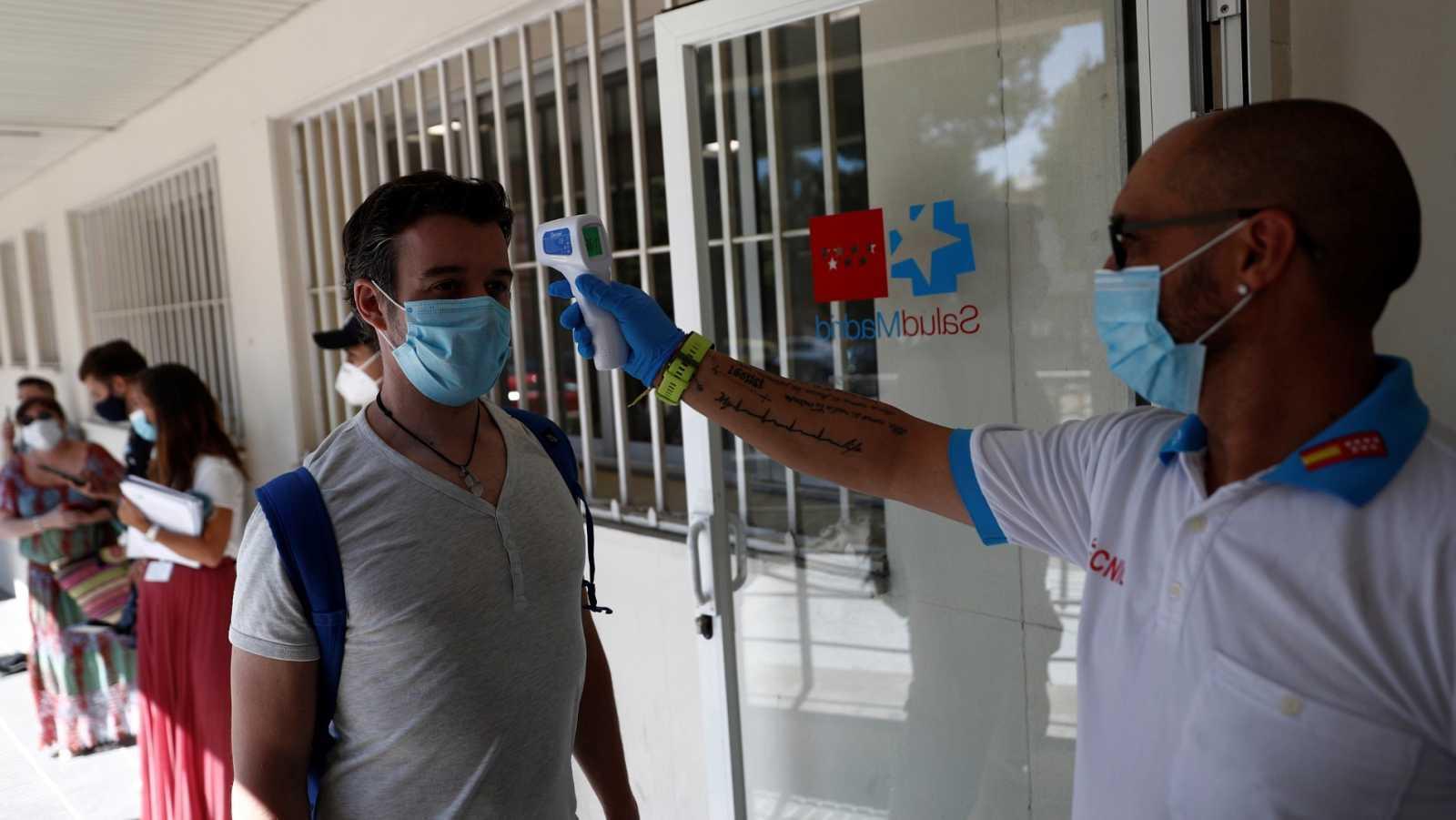 Un sanitario toma la temperatura a una persona que espera para realizarse una prueba de PCR en Madrid
