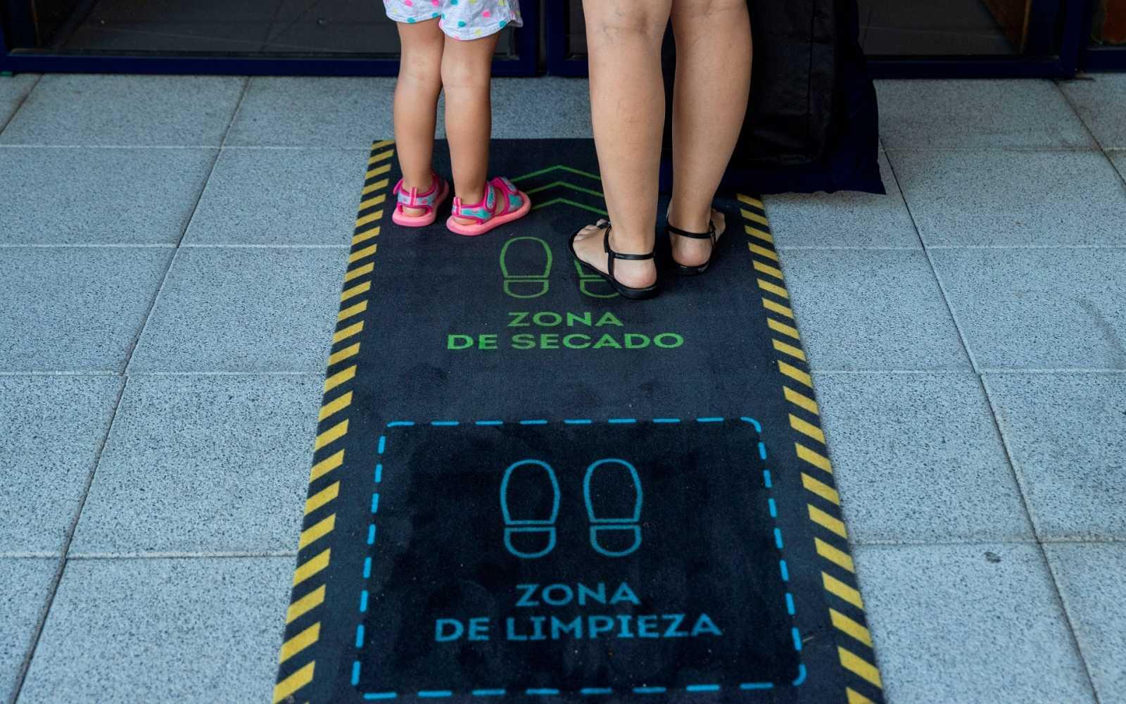 Una madre y su hija se limpian los zapatos en la puerta de una escuela infantil en Madrid