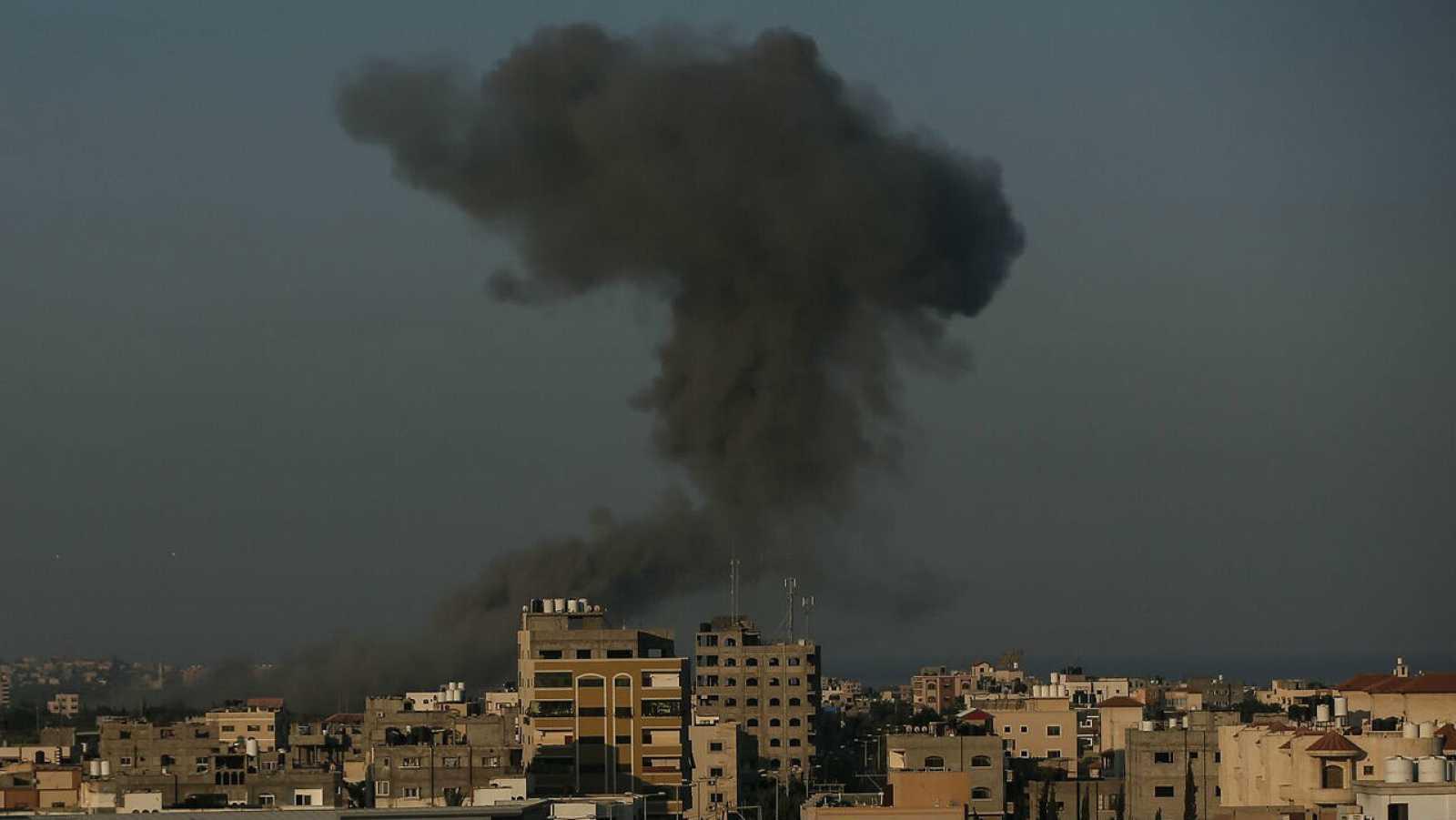Humo entre edificios después de que aviones de guerra pertenecientes al ejército israelí llevaran a cabo ataques aéreos sobre la ciudad de Gaza.