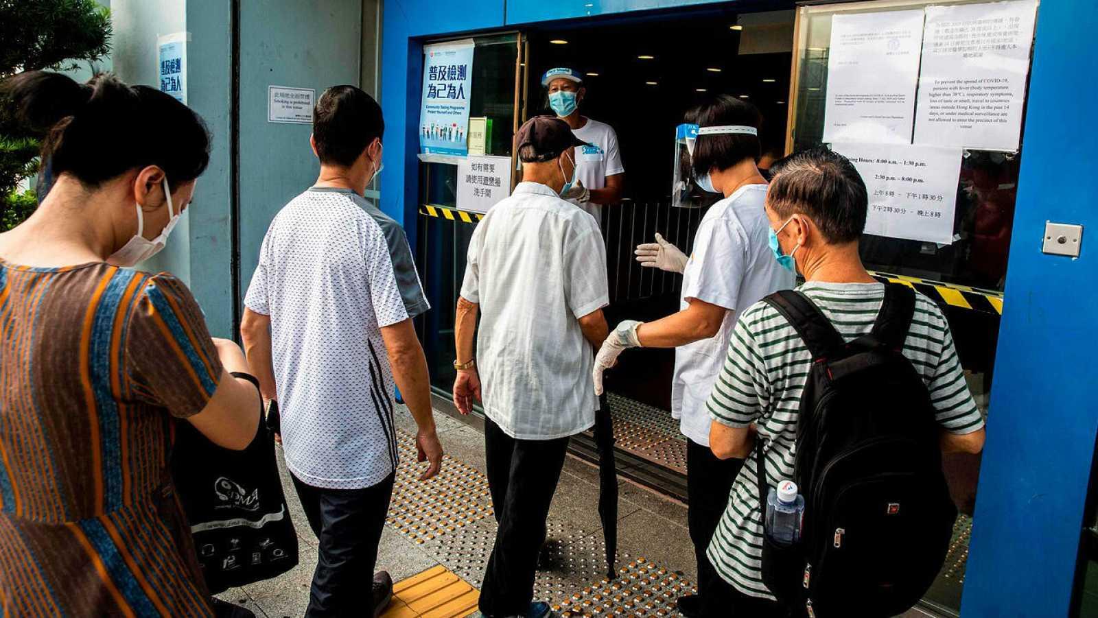 La gente espera en una cola en un centro de pruebas de coronavirus COVID-19 en Hong Kong.