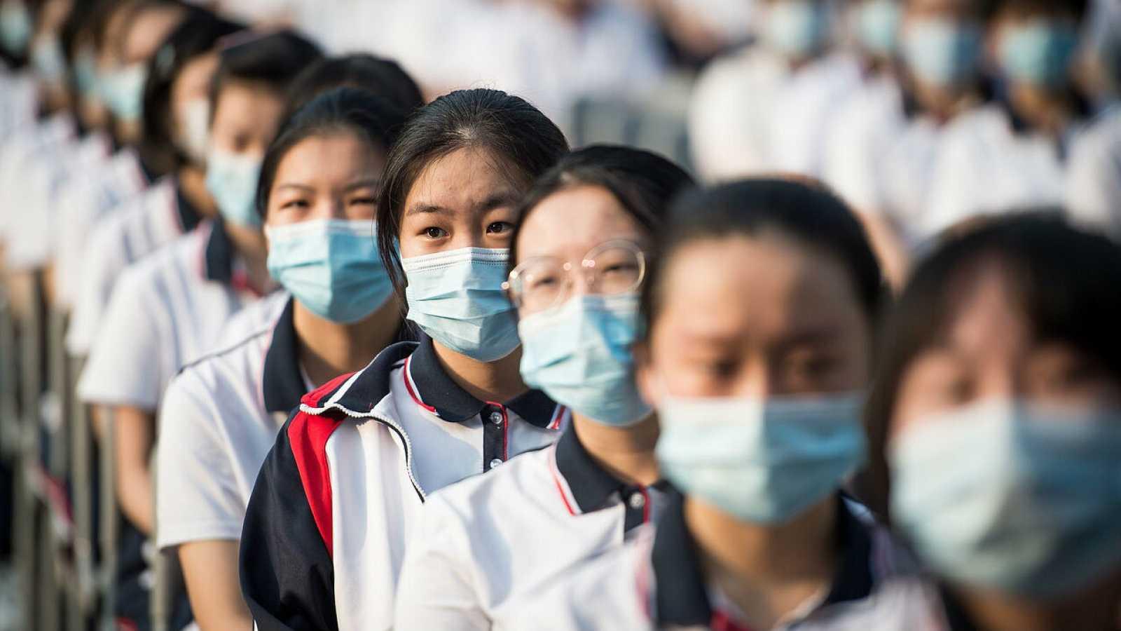 Estudiantes de la escuela secundaria de Wuhan con mascarillas se sientan mientras asisten a la ceremonia del nuevo semestre de otoño en Wuhan, provincia de Hubei, China.