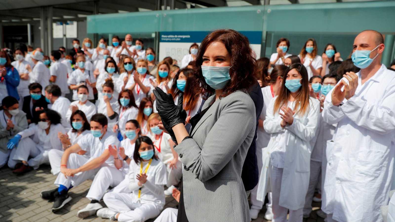 La presidenta madrileña aplaude en el acto de cierre del hospital de Ifema