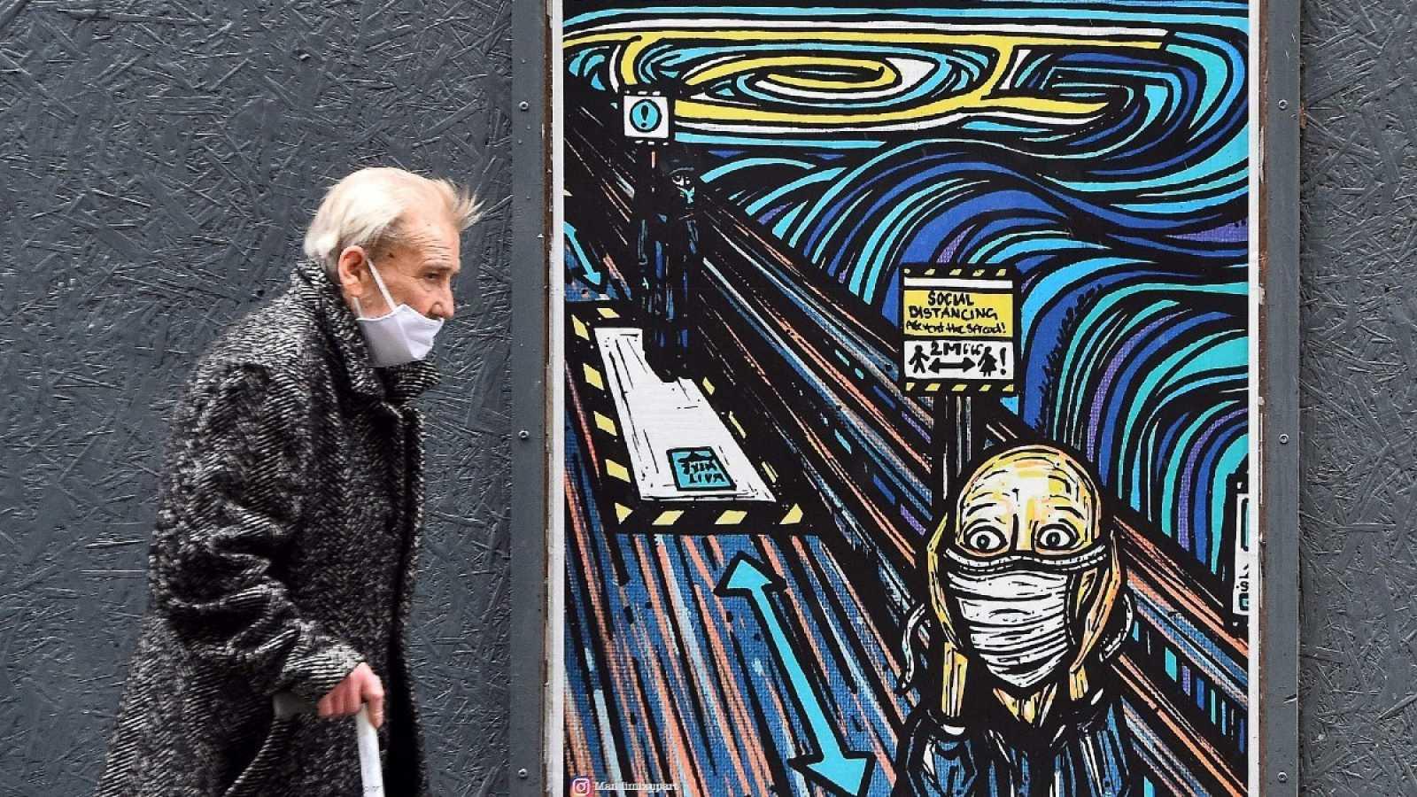 Un peatón con mascarilla pasa por delante de un grafiti que parodia la obra de 'El Grito' de Munch en tiempos de pandemia, en Glasgow.