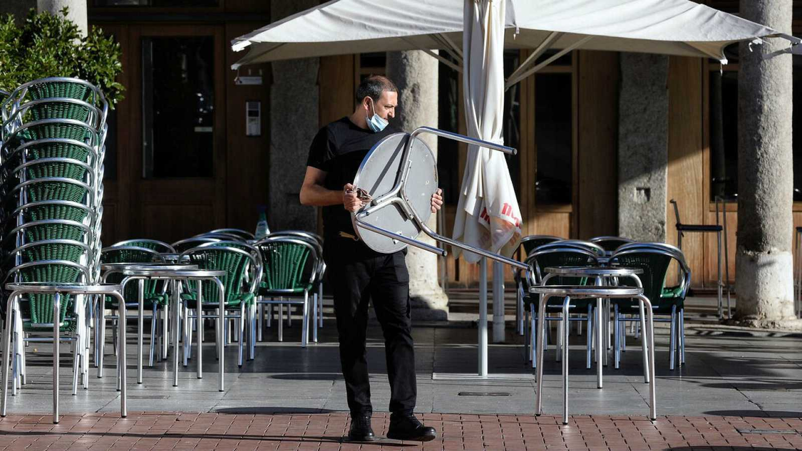 Un camarero coloca las mesas en una terraza en Valladolid.