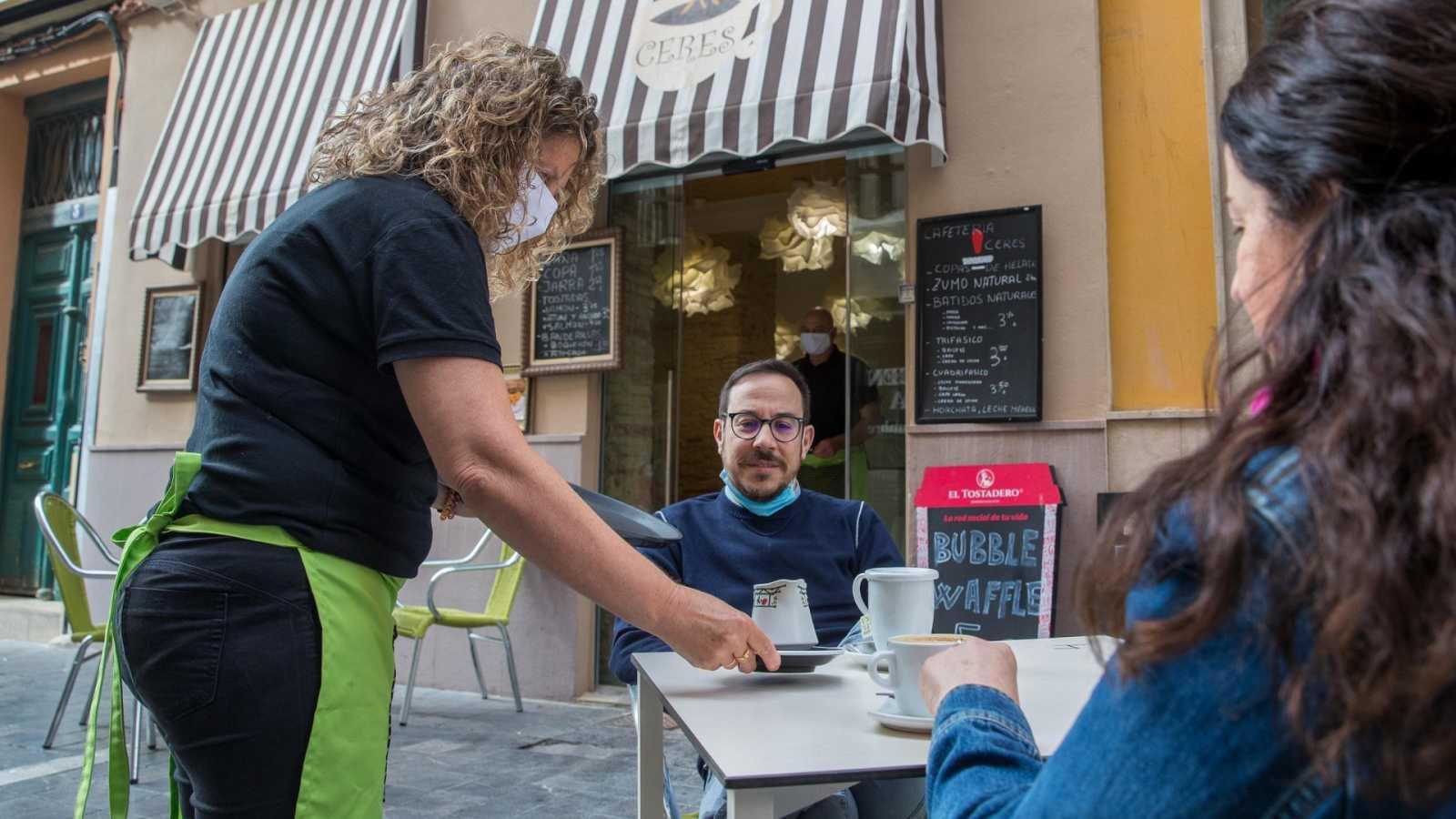 Una camarera atiende a una pareja en la terraza de una cafetería en Zaragoza