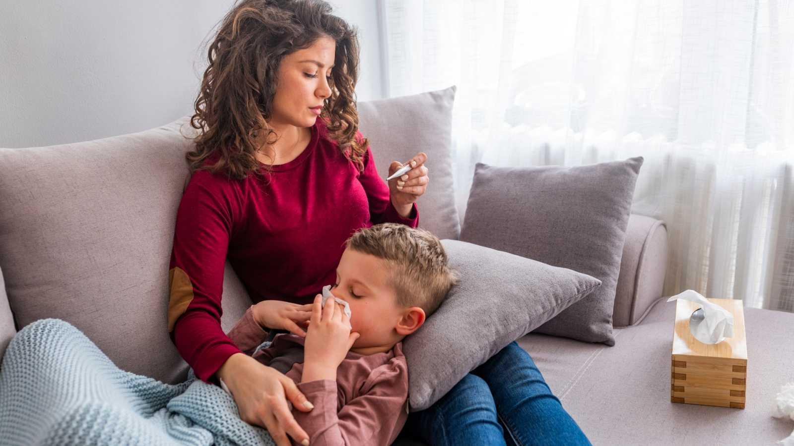 Una madre cuida de su hijo y le toma la temperatura