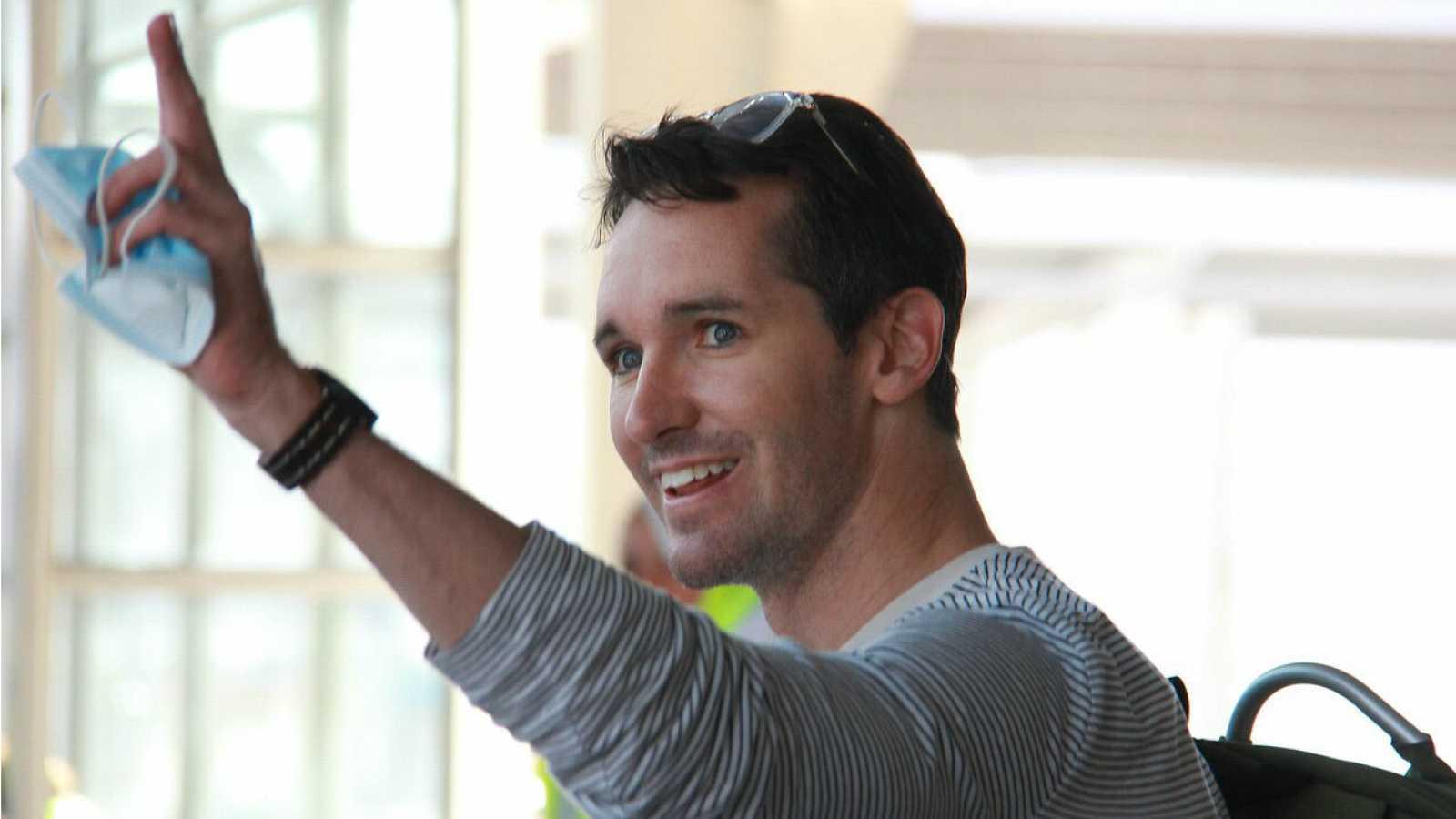 El periodista de la Australian Broadcasting Corporation, Bill Birtles, saludando a su llegada a Sydney después de salir de China por temor a ser arrestado.