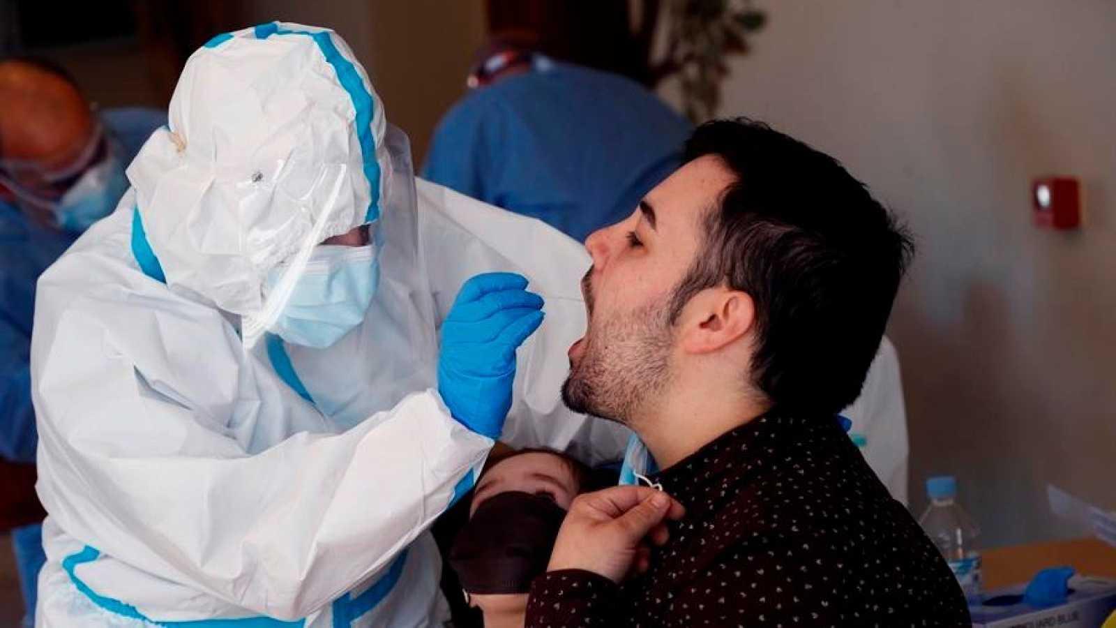 Un sanitario realiza una prueba PCR a un joven