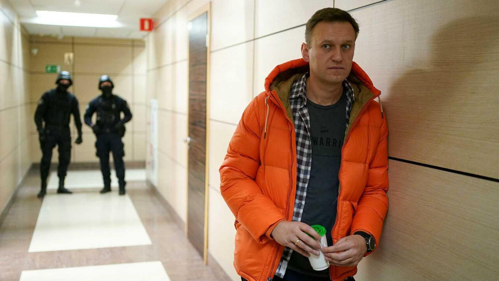 El líder de la oposición rusa, Alexei Navalny, de pie cerca de los agentes del orden en un pasillo de un centro de negocios, que alberga la oficina de su Fundación Anticorrupción (FBK), en Moscú.