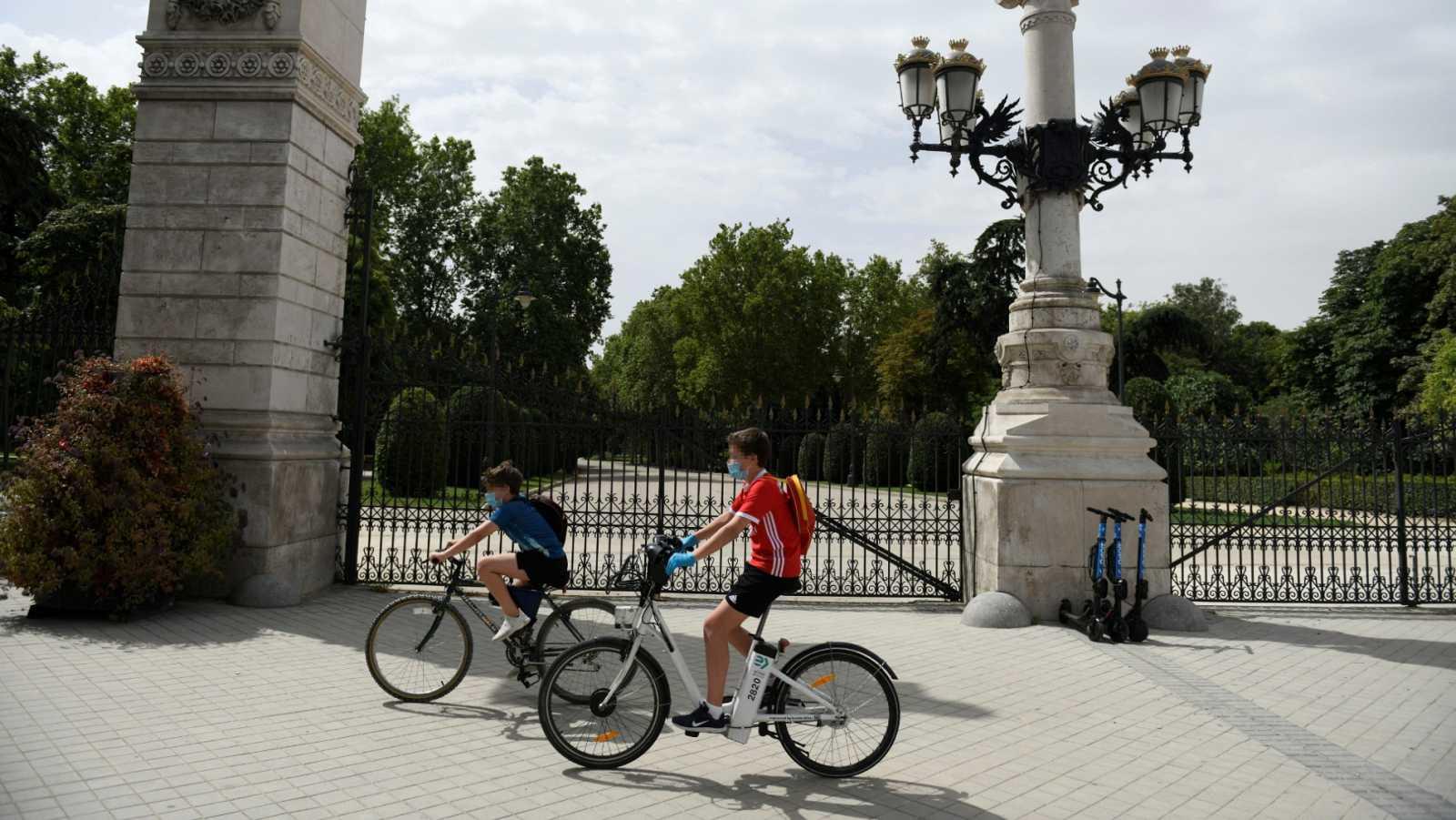 Dos jóvenes montan en bici en el exterior del parque del Retiro en Madrid