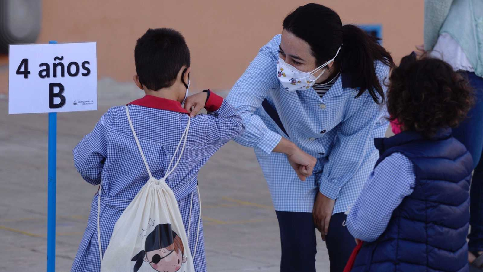Una profesora y un alumno se saludan en un colegio de Valladolid.