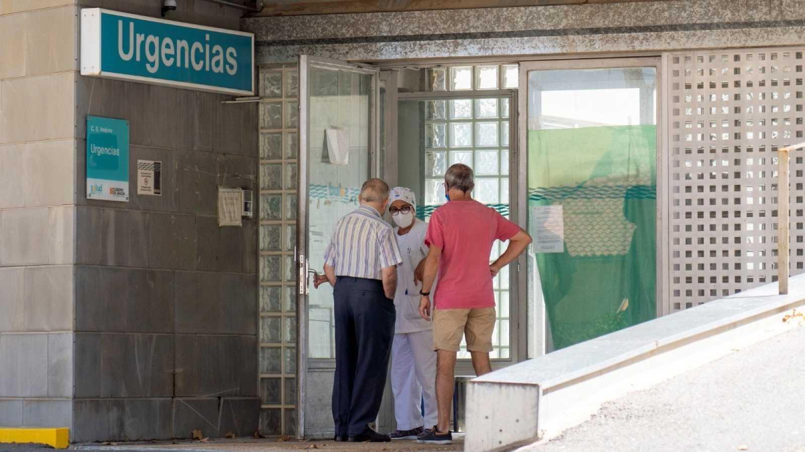 Una trabajadora del centro de salud de Andorra (Teruel) habla con dos vecinos que se acercan a la puerta de Urgencias