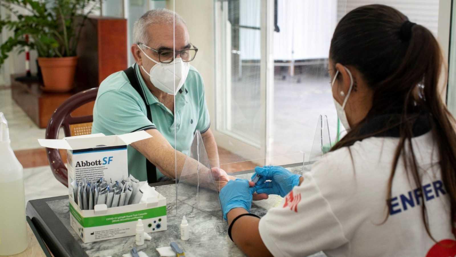 Una enfermera toma una muestra de sangre a un ciudadano para un test serológico en el Centro de Día de Mayores de La Isleta, Gran Canaria.