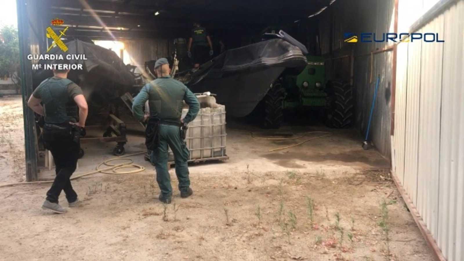 Dos agentes de la Guardia Civil observan una narcolancha incautada en la Operación Tortilla