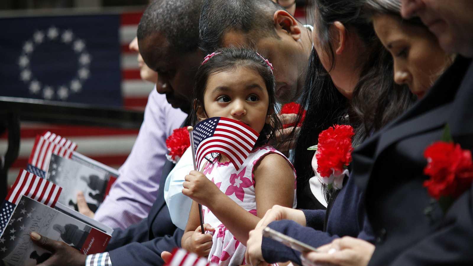 La hija de un inmigrante sostiene una bandera estadounidense.
