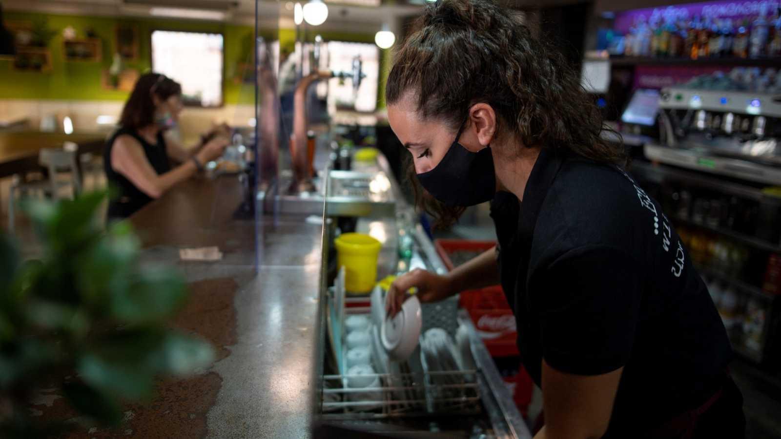 Una camarera seca la vajilla en un bar