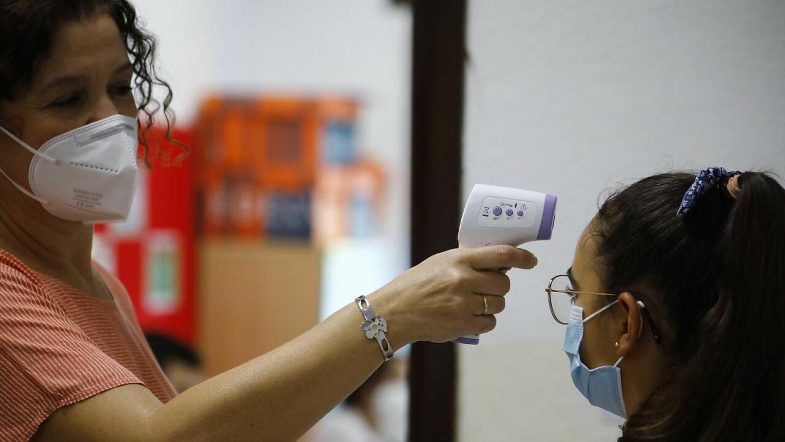 Una profesora toma la temperatura a una alumna a la llegada al colegio San Rafael del Obispo en Córdoba hoy en el comienzo del n