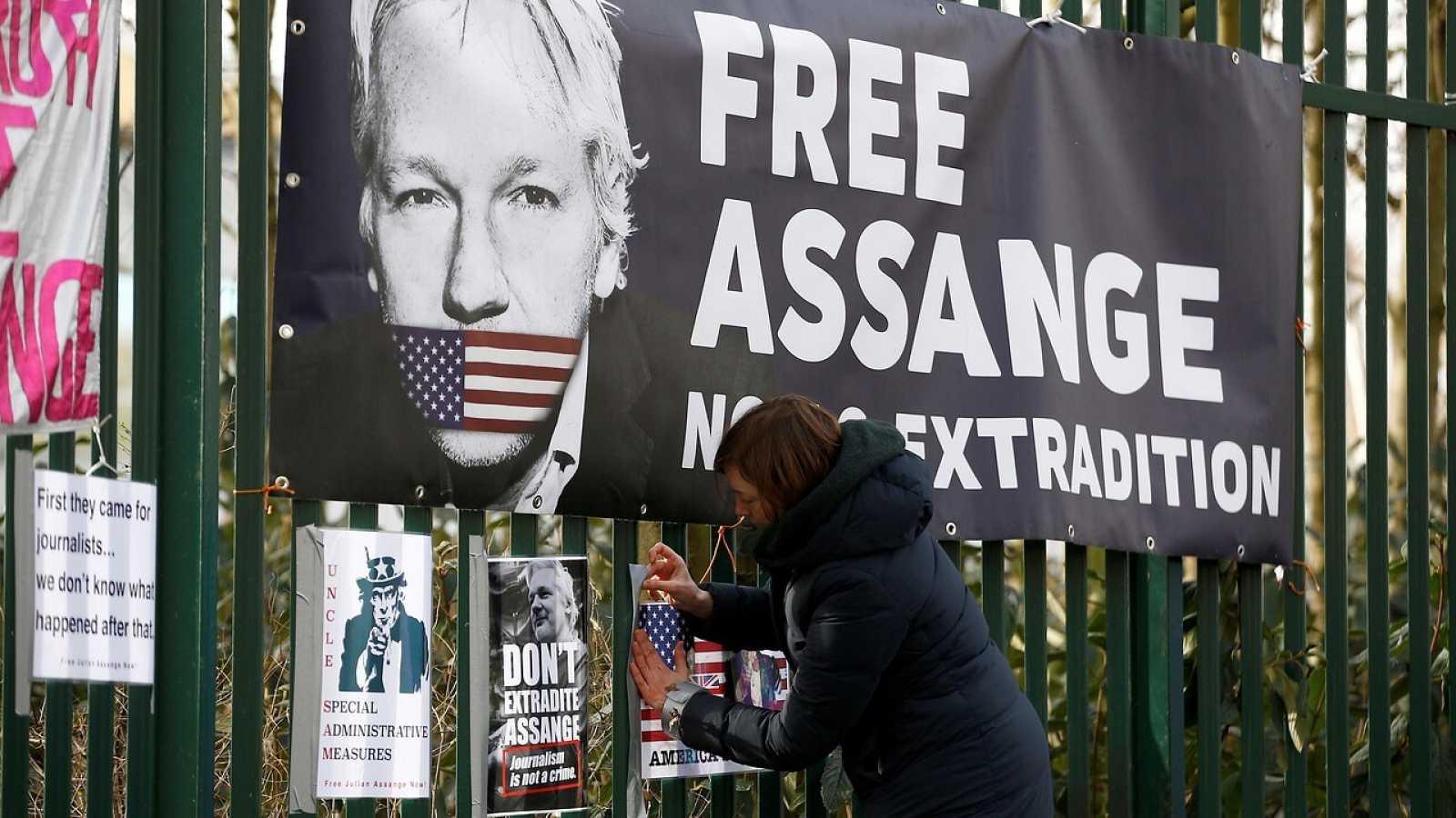 Una mujer pone  un cartel en la valla de Woolwich Crown Court en favor de Assange