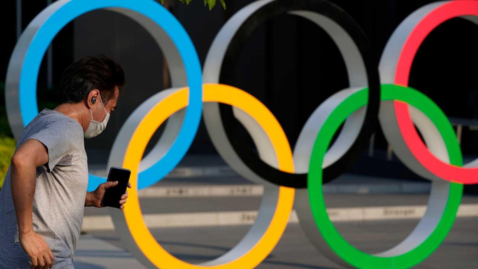 Un hombre corre por delante de los aros olímpicos