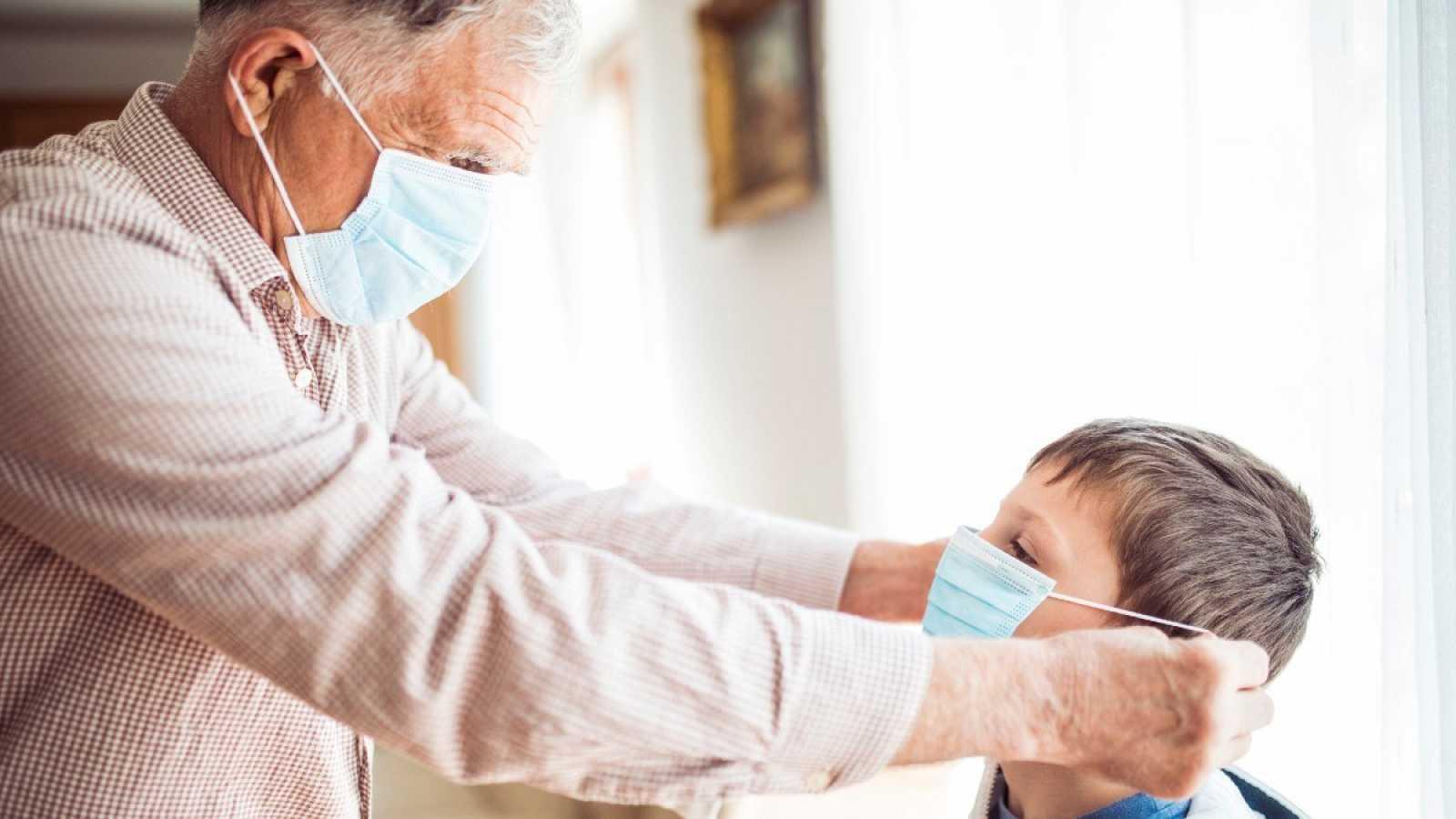 Un abuelo coloca la mascarilla a su nieto