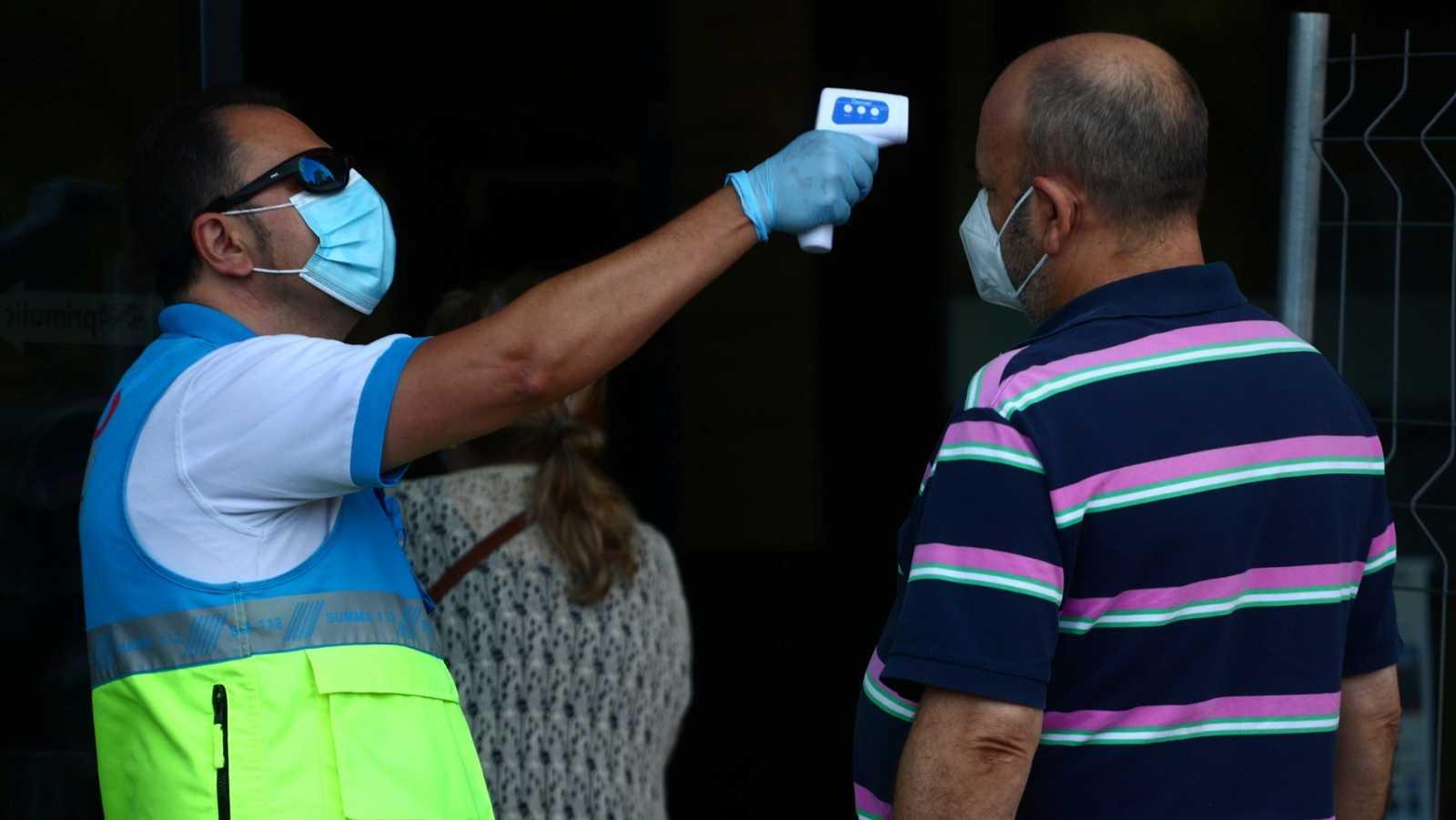 Toma de temperatura a la entrada de un centro cultural de Vallecas donde se realizan test de antígenos del coronavirus