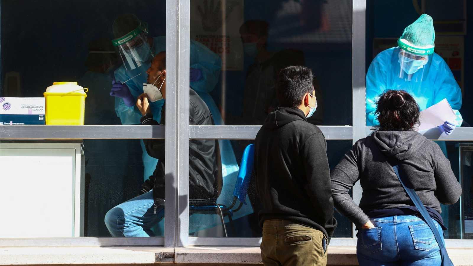 Un sanitario toma una muestra de hisopo a un paciente para la prueba de antígenos en Orcasitas (Madrid)