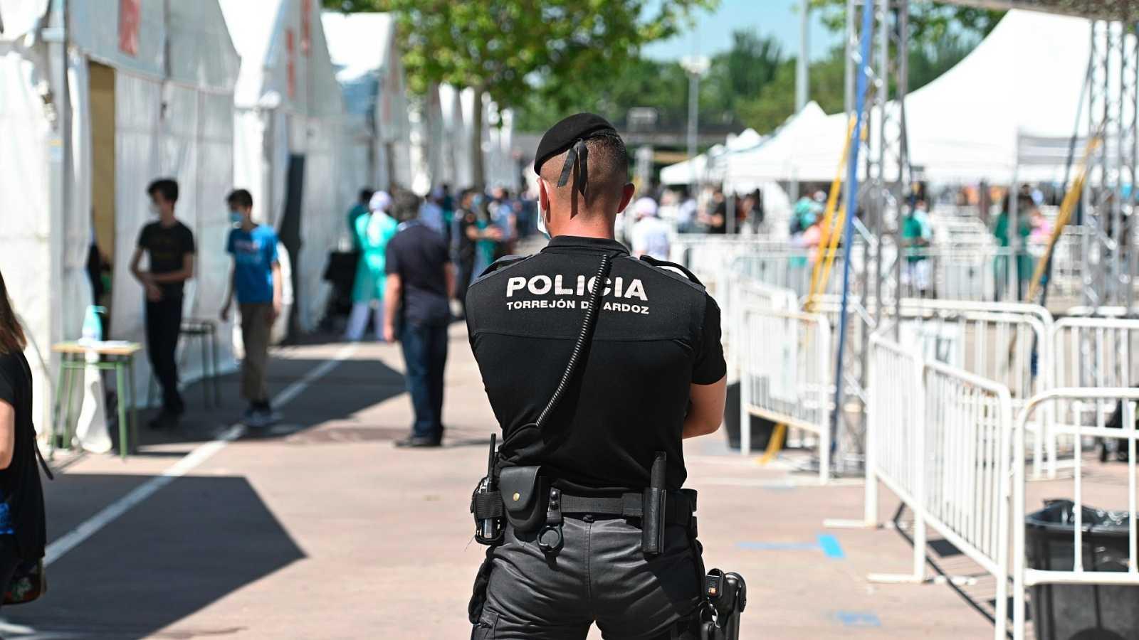 Un Policía Nacional vigila la realización de test de seroprevalencia en el recinto ferial de Torrejón de Ardoz.