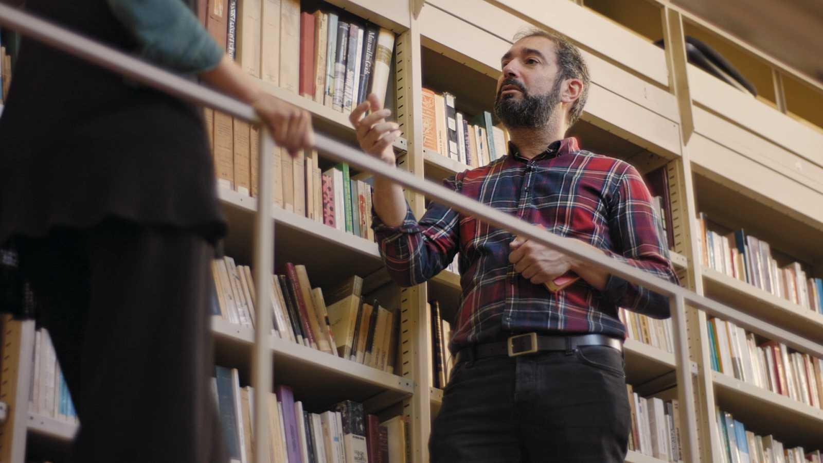 Pere Estupinyà, de pie, en una entrevista para El Cazador de Cerebros dentro de una biblioteca