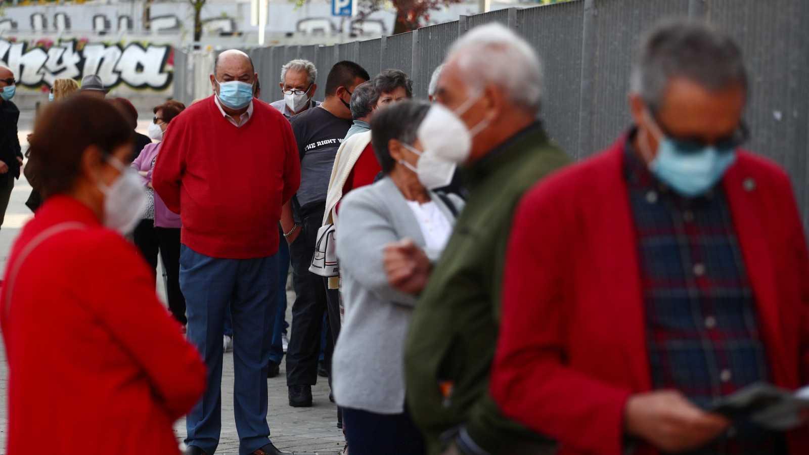 Varias personas hacen cola en Vallecas, Madrid, para hacerse el test de antígenos
