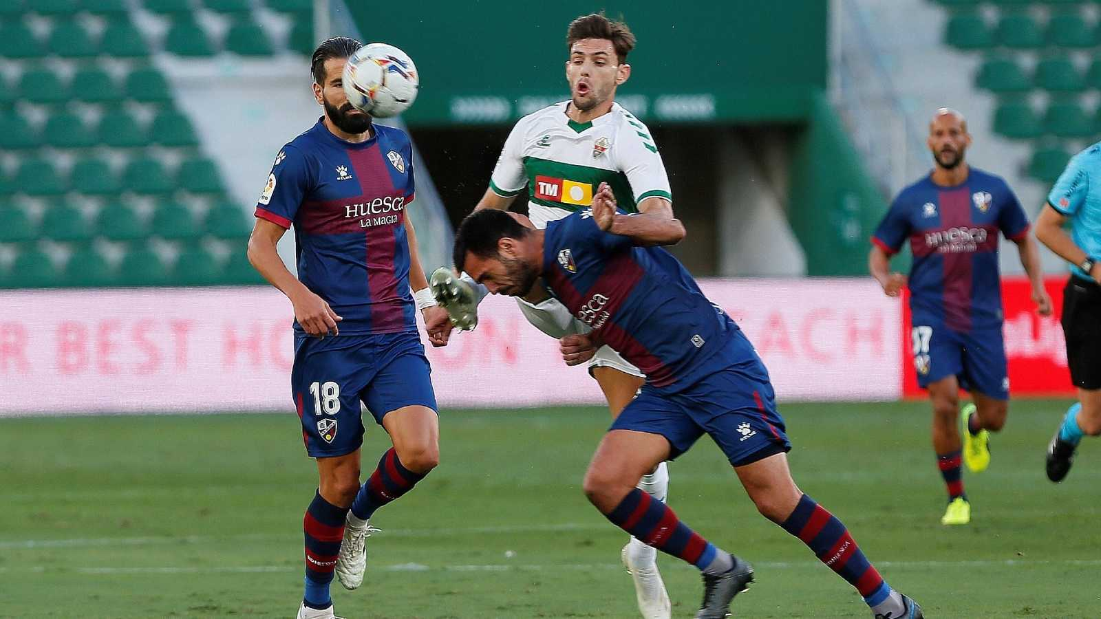 l delantero argentino del Elche Lucas Boyé (c) pelea un balón con el defensa del Huesca Pablo Insua