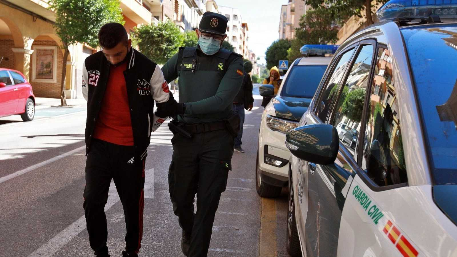 Un agente de la Guardia Civil traslada a uno de los diez detenidos