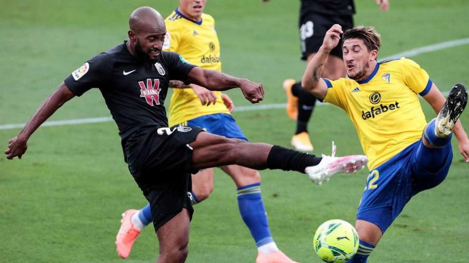 El defensa francés del Granada CF, Dimitri Foulquier (i) pelea un balón con el defensa del Cádiz Luis Espino.