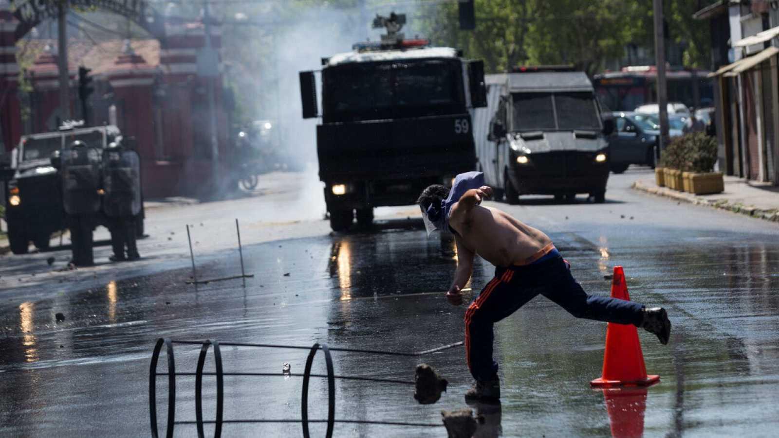 Manifestantes se enfrentan con las Fuerzas Especiales de Carabineros en la entrada de la Clínica Santa María en Santiago (Chile).