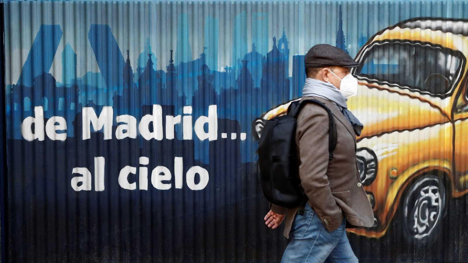 Una persona con mascarilla camina por una calle de Madrid