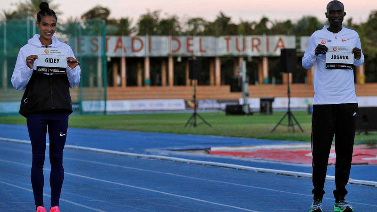 La atleta etíope Letensebet Gidey y el atleta ugandés Joshua Cheptegei, que este miércoles tratarán de batir los récord del mundo de los 5.000 y 10.000 metros lisos respectivamente, en el estadio Jardin del Túria de València, posan con sus dorsales.