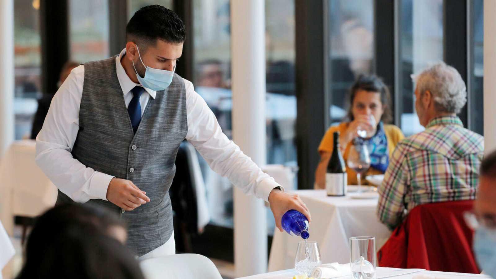Un camarero llena un vaso en un restaurante en Manhattan, Nueva York, Estados Unidos.