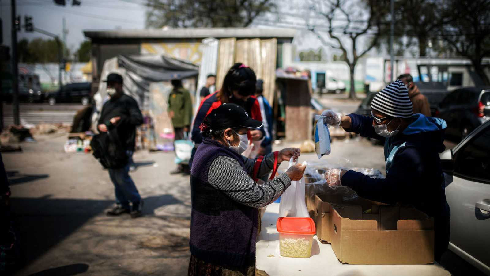 Una mujer obtiene alimentos hoy en un comedor comunitario, en una villa de la Ciudad de Buenos Aires.
