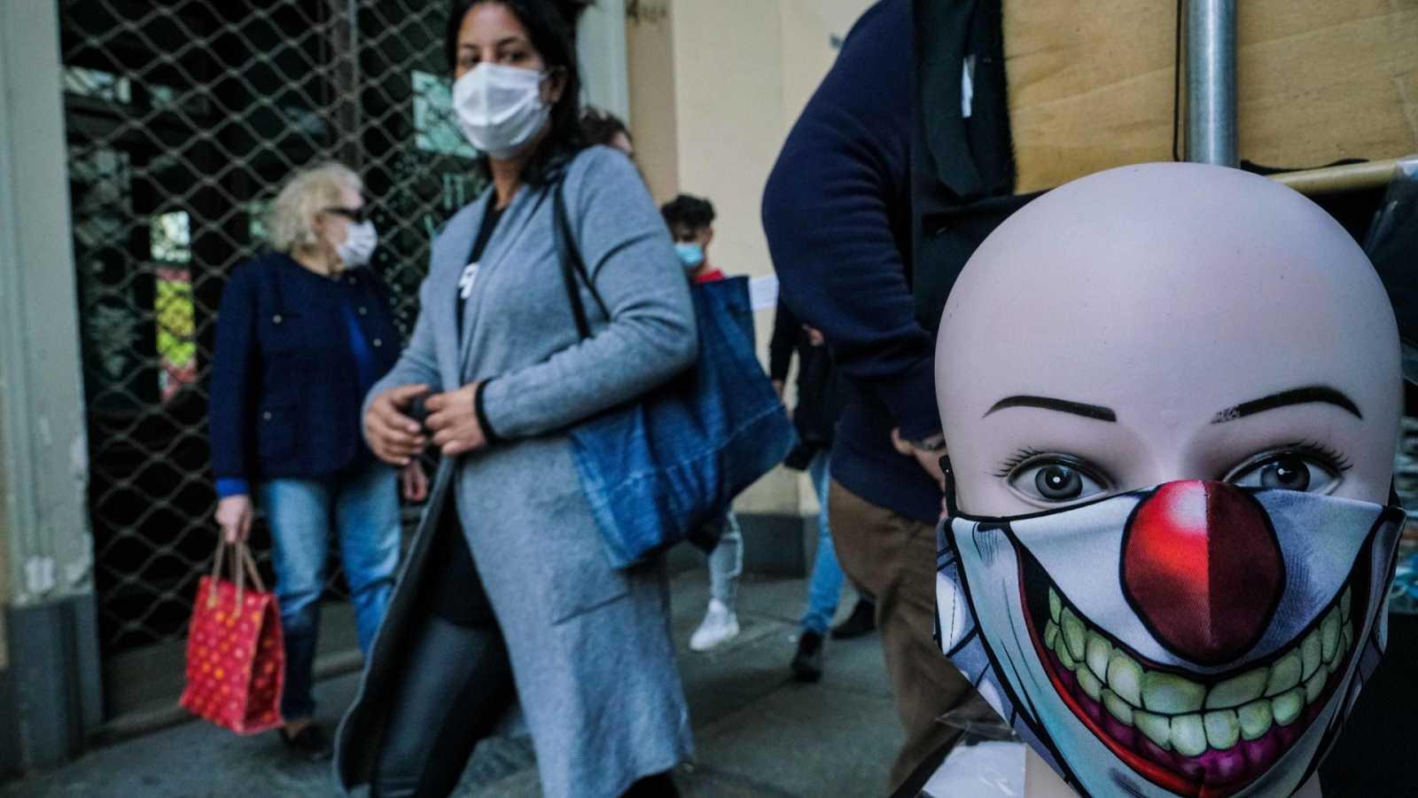 Una mujer mira un maniquí con mascarilla en Turín